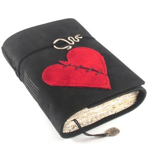Image of a black leather-bound book with a red heart on the front. The heart has a diagonal line of black stitching across it. Image courtesy of kreativlink on DeviantArt.
